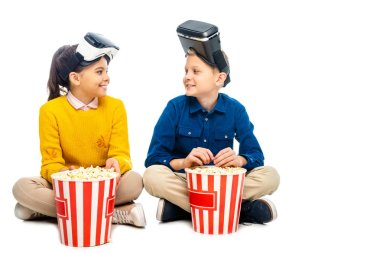 Smiling kids with virtual reality headsets on heads sitting near striped popcorn buckets and looking at each other isolated on white stock vector