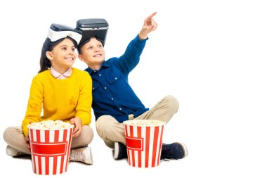Smiling boy with virtual reality headsets on head pointing with finger and cute schoolgirl holding striped popcorn bucket isolated on white stock vector