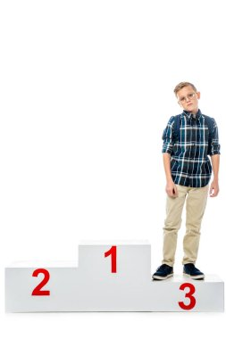 disappointed boy standing on winner podium and looking at camera isolated on white
