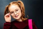 roztomilá školačka dotýká brýle a při pohledu na fotoaparát na černém pozadí