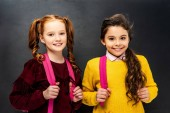 Fotografie Lächelnde Schulmädchen mit rosa Rucksäcken schauen in die Kamera auf schwarzem Hintergrund