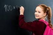 školačka s růžový batoh psaní na tabuli křídou a při pohledu na fotoaparát
