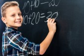 s úsměvem chlapce psaní matematický příklad na tabuli křídou a při pohledu na fotoaparát