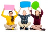smiling kids sitting and holding speech bubbles over heads isolated on white