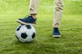 oříznutý pohled chlapce s nohou stojící na fotbalový míč na trávníku