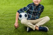 oříznutý pohled usměvavý chlapec drží fotbalový míč a sedí na trávníku