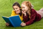 scolare che si trova sul prato e libro di lettura sorridenti
