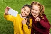 s úsměvem školačky, přičemž selfie a ukazuje palcem a znamení míru na trávníku
