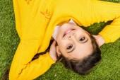 felülnézet mosolygó iskoláslány a kezét a feje látszó-on fényképezőgép, és feküdt a gyepen sárga pulóver