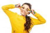 Fotografie roztomilá školačka v žlutém svetru, při pohledu na fotoaparát a vykazuje známky mír s rukama maloval barevné nátěry izolované na bílém