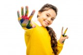 selective focus of smiling schoolgirl showing hand painted in colorful paints and looking at camera isolated on white