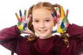 Nahaufnahme von niedlichen Schulmädchen, die in die Kamera schauen und Hände zeigen, die in bunten Farben isoliert auf weiß gemalt sind