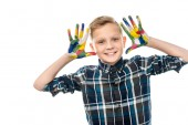 smiling boy showing hands painted in colorful paints and looking at camera isolated on white