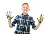 roztomilý chlapec při pohledu na fotoaparát a ukazuje rukou malované v pestré barvy izolované na bílém