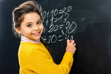 smiling schoolgirl writing on blackboard with chalk and looking at camera