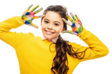 Smiling schoolgirl in yellow sweater looking at camera and showing hands painted in colorful paints isolated on white stock vector