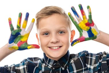 Close up view of cute boy looking at camera and showing hands painted in colorful paints isolated on white stock vector