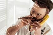 Fotografie gut aussehend bärtiger Mann in Gläsern Gespräch am Telefon und rauchende Zigarre