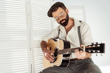 handsome bearded man in cap and glasses sitting and playing guitar near white room divider