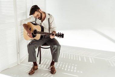 handsome bearded man in cap sitting on chair and playing guitar near white room divider