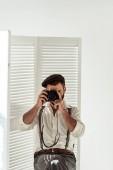 Szakállas férfi ül fehér térelválasztó bevétel mozi-val vintage filmes fényképezőgép