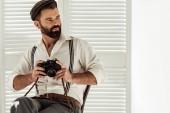 szép szakállas ember ül a széken, és a gazdaság vintage filmes fényképezőgép