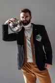 Fotografie vousatý muž držící disco koule na rameni a při pohledu na fotoaparát izolované Grey