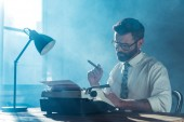 Fotografie bearded journalist in glasses sitting at table, holding cigar and looking at vintage typewriter near window