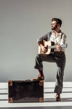bearded musician in cap near vintage suitcase playing acoustic guitar on grey background