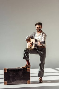 smiling bearded man in cap near vintage suitcase playing acoustic guitar and looking at camera on grey background