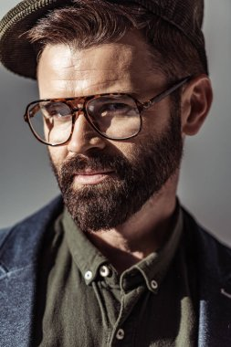 Close up view of handsome bearded man in glasses and cap looking at camera isolated on grey stock vector