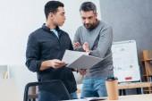 ernsthafte Geschäftsleute halten Ordner mit Papieren und diskutieren Projekt im Büro