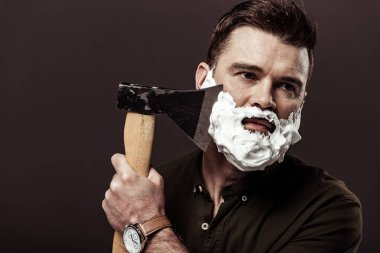 handsome bearded man in brown shirt shaving with ax isolated on brown