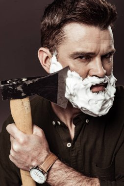 serious handsome man with foam on face shaving beard with ax isolated on brown