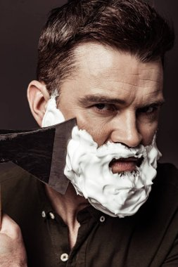 close up of serious handsome bearded man shaving with ax while looking at camera isolated on brown