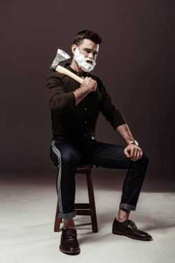 handsome bearded man sitting on chair and holding ax