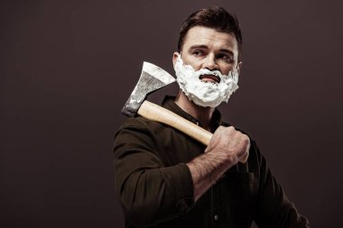 handsome bearded man with shaving foam on face holding ax isolated on brown