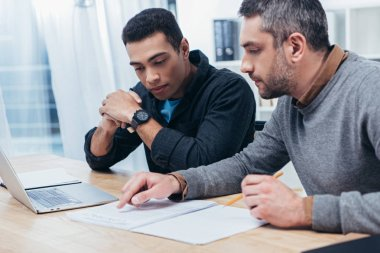concentrated male coworkers using laptop and working with papers in office