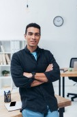 handsome young mixed race businessman standing with crossed arms and smiling at camera in office