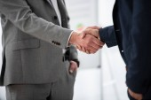 Photo cropped shot of businessmen in formal wear shaking hands in office