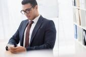 vážný mladý podnikatel v brýlí pomocí smartphone v kanceláři