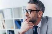 Fotografie handsome bearded businessman in eyeglasses holding hand on chin and looking away in office