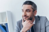 Fotografie portrait of handsome smiling bearded businessman with hand on chin looking away in office