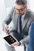 Fotografie vysoký úhel pohled pohledný podnikatel v brýlí pomocí digitálních tabletu s obchodní grafy a grafy