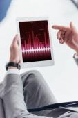 Fotografie částečný pohled podnikatel pomocí digitálních tabletu s obchodní grafy na obrazovce