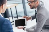 Fotografie Oříznout záběr podnikatel v brýlích ukazuje digitální tablet s prázdnou obrazovkou na mužské kolegy v kanceláři