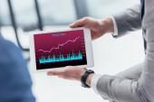 částečný pohled podnikatel drží digitální tabletu s obchodními grafů na obrazovce