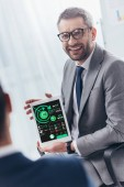 Fotografie smiling businessman in eyeglasses holding digital tablet with charts and graphs on screen