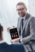 smiling businessman in eyeglasses holding digital tablet with charts and graphs on screen