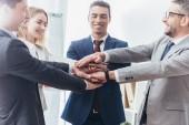 Happy profesionální obchodní tým překrývání ruce v úřadu